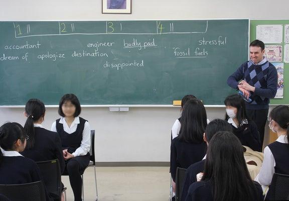 黒板に背を向けた生徒が、ヒントを聞いて英単語を言い当てるゲーム