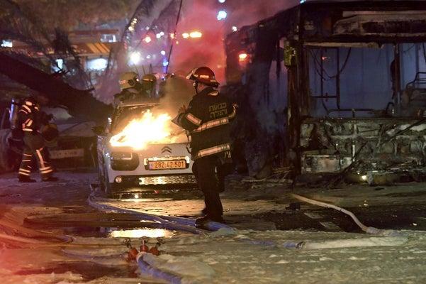 11日、イスラエル・テルアビブ近郊で、ガザ地区からのロケット弾を受けて炎上する車(AP)