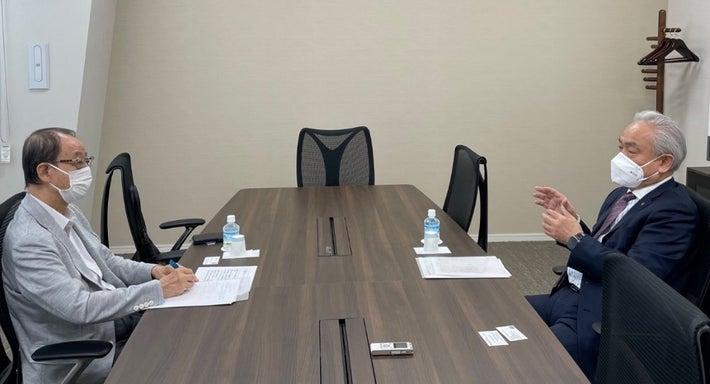 筆者のインタビューに応じる尾崎会長(右)